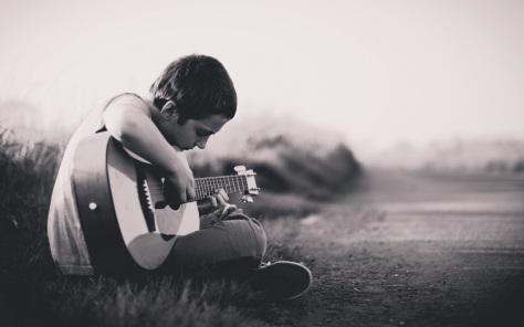 Young boy mediating playing guitar
