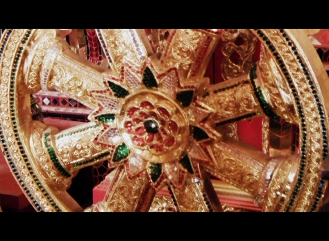 Close-up of golden dharma wheel embedded with jewels
