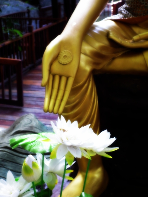 Golden Buddha with hand gesture of offering lotus flower